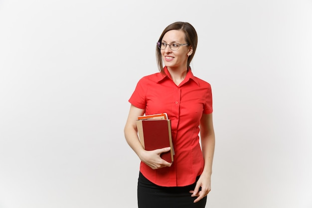 Portrait of young business teacher woman in red shirt, skirt and glasses looking aside, holding books in hands isolated on white background. education or teaching in high school university concept.