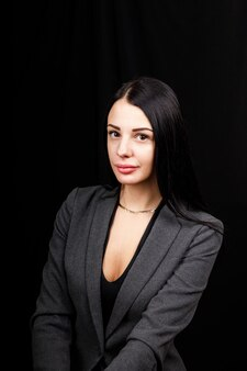 Portrait of young business woman in  a grey jacket on black background.