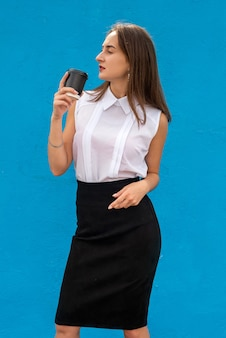 Portrait of young business woman holding cup of coffee isolated on blue