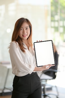 Portrait of young business woman showing blank screen digital tablet while standing in office room