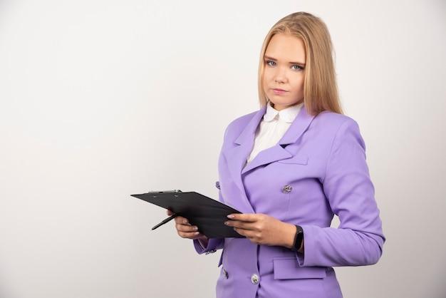 Ritratto di giovane donna di affari che sta e che tiene appunti.