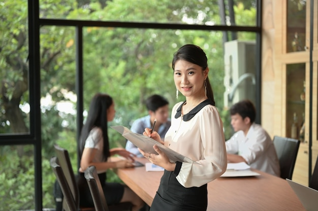 Portrait of young business woman standing at modern startup office, blured team in meeting background.