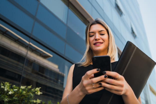 Ritratto di giovane donna d'affari utilizzando il suo telefono cellulare in piedi fuori dagli edifici per uffici. concetto di affari e successo.