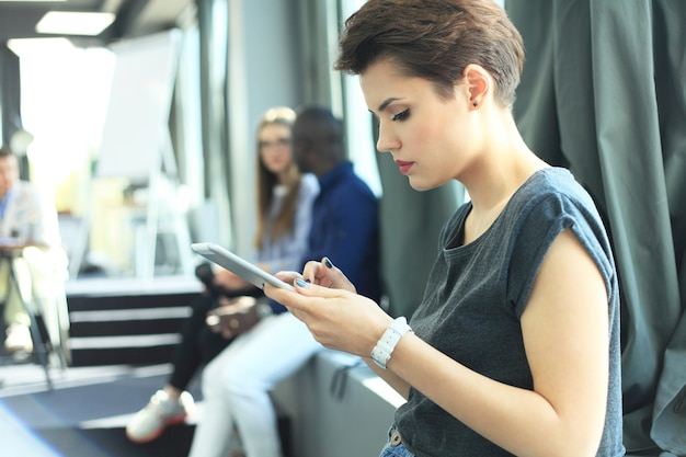 現代のスマートフォンの手を使用して肖像画の若いビジネス女性。日当たりの良いオフィスで作業過程でsmsメッセージを読んでいる女の子。水平方向のぼやけ