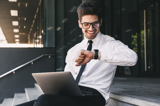 Portrait of young businessman dressed in formal suit sitting outside glass building with laptop, and looking at his wrist watch
