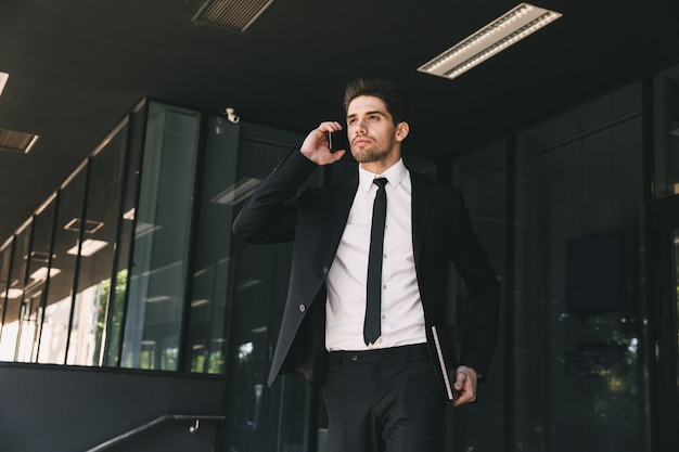 Portrait of young businessman dressed in formal suit standing outside glass building, and speaking on smartphone