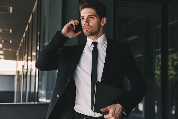 Portrait of young businessman dressed in formal suit walking outside glass building, and talking on mobile phone