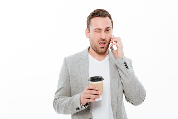 Portrait of young businessman drinking takeaway coffee while having pleasant mobile conversation on cellphone and winking, over white wall