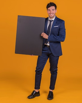Portrait of a young businessman holding blank black placard on an orange background