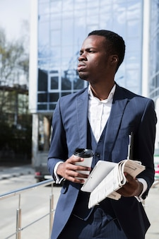 Portrait of a young businessman holding digital tablet; newspaper and disposable coffee cup