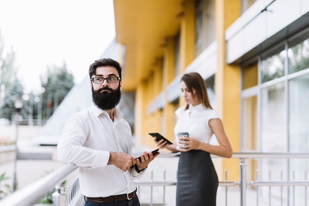 Portrait of young businessman holding digital tablet with businesswoman standing at background