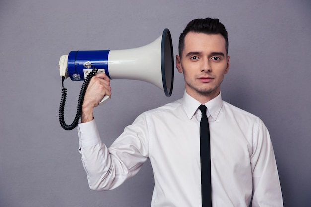 Portrait of a young businessman holding loudspeaker on gray wall