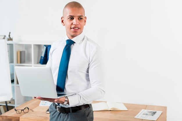 Portrait of a young businessman holding an open laptop in hand looking away