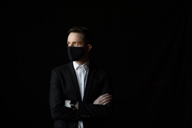 그의 팔을 교차 한 벌에 세로 젊은 사업가 얼굴 마스크를 착용