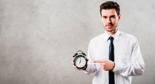 Portrait of a young businessman pointing at black alarm clock standing against grey concrete wall