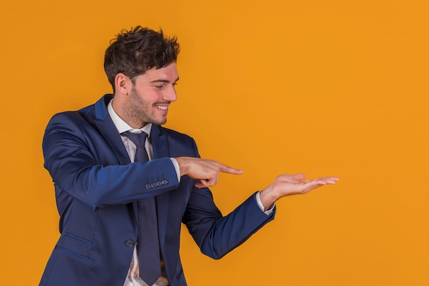 Portrait of a young businessman pointing his finger at something against an orange background