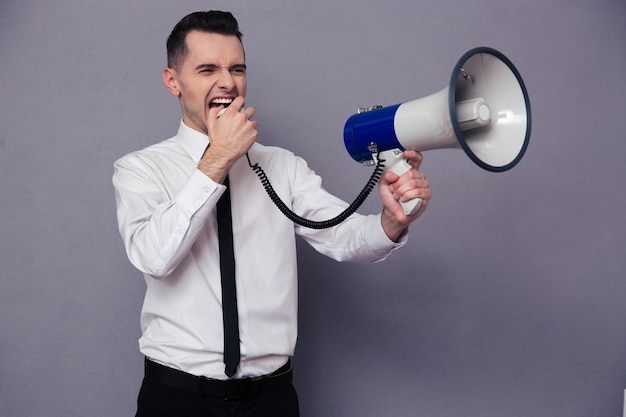 Portrait of a young businessman screaming in megaphone over gray wall