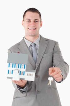 Portrait of a young businessman showing a miniature house and ke