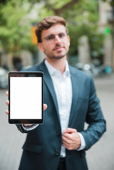 Portrait of a young businessman showing white screen display digital tablet