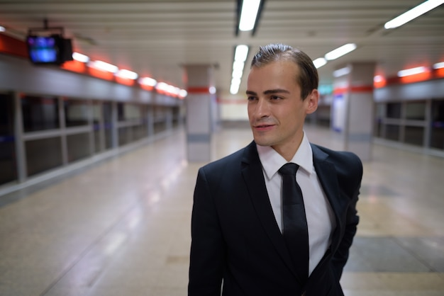 Portrait of young businessman smiling at train station