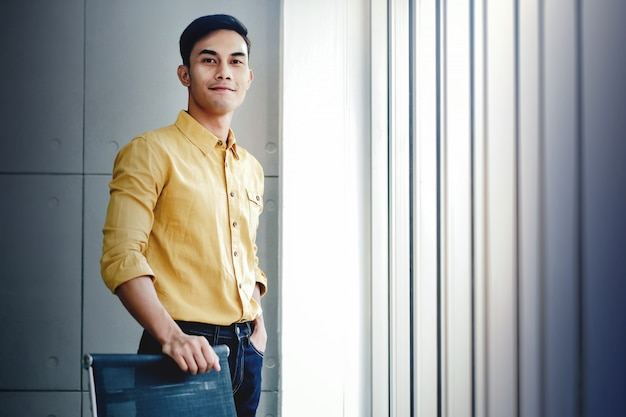 Portrait of young businessman standing by the window in office