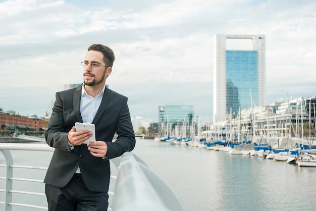 Portrait of a young businessman standing near the harbor holding mobile phone in hand looking away