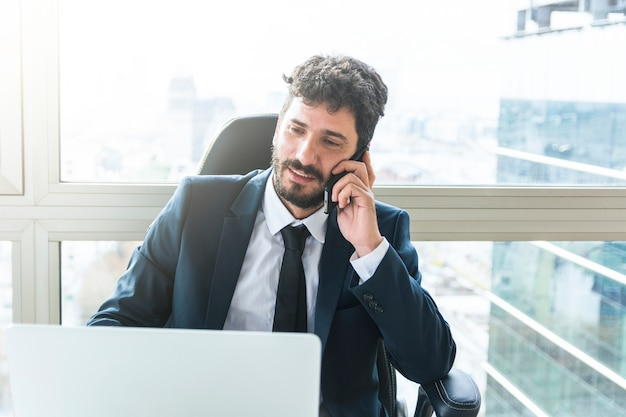Portrait of young businessman talking on mobile phone near the window