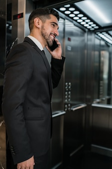 Portrait of young businessman talking on the phone at the hotel elevator. business travel concept.