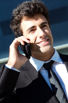 Portrait of young businessman talking with smartphone