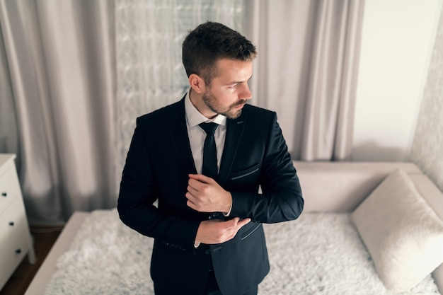 Portrait of young businessman tying cufflinks on jacket and looking away.