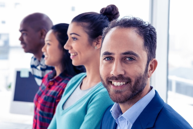 Portrait of young businessman with colleagues standing in creative office