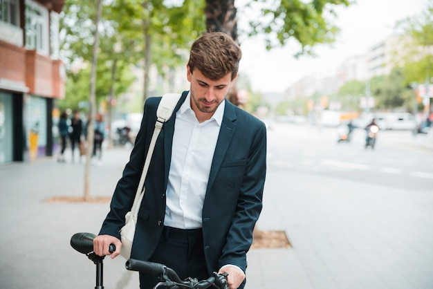 Portrait of a young businessman with his bicycle standing on street
