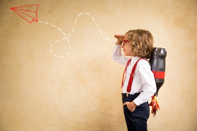 Portrait of young businessman with jet pack in office