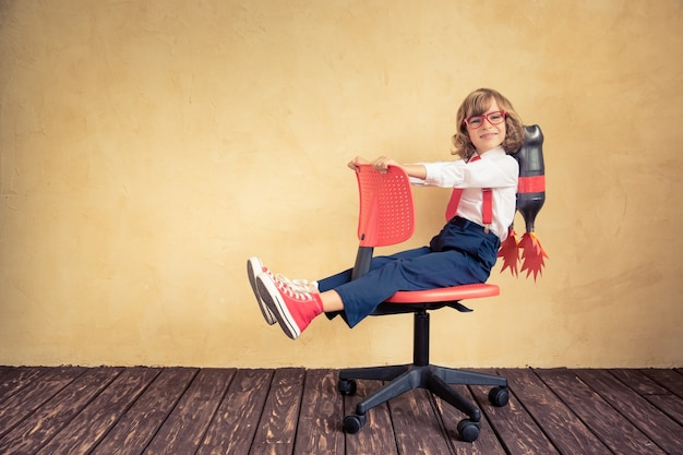 Portrait of young businessman with jet pack riding office chair