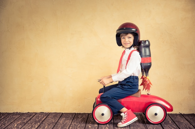 Portrait of young businessman with jet pack riding retro car