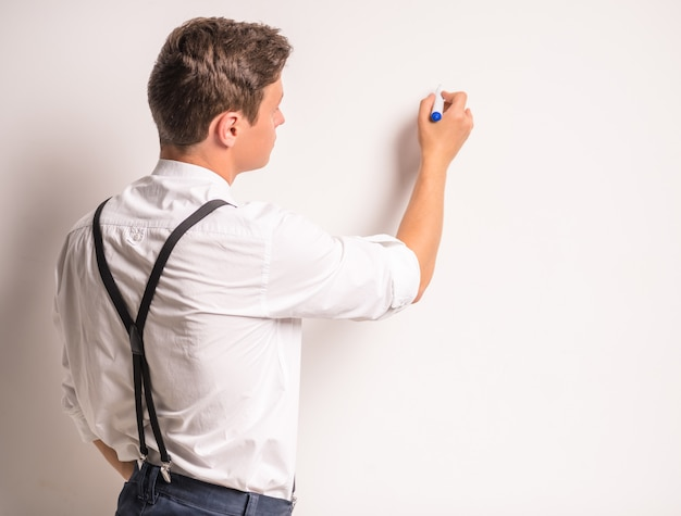 Portrait of a young businessman, write a marker on the wall