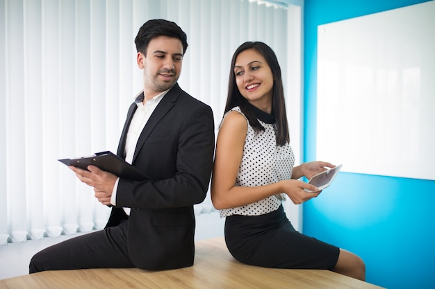 Portrait of young businesspeople sitting on table and flirting