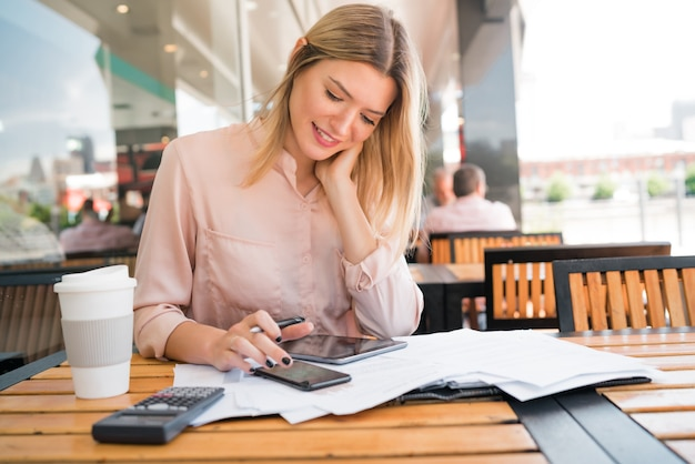 Portrait of young businesswoman checking paperwork and working at coffee shop