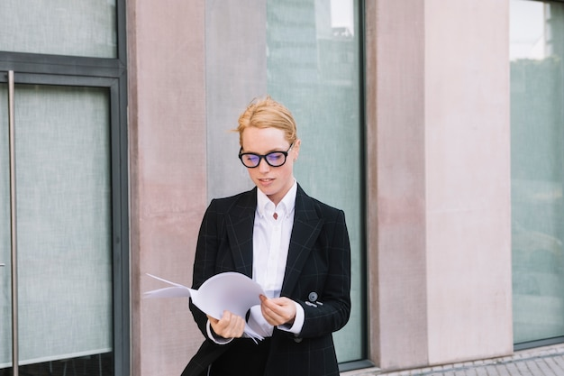 Portrait of a young businesswoman checking white paper
