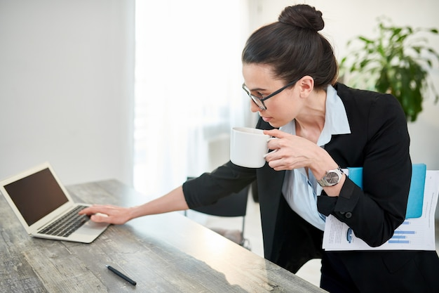 Portrait of young businesswoman drinking coffee and morning and turning on laptop at workplace, copy space