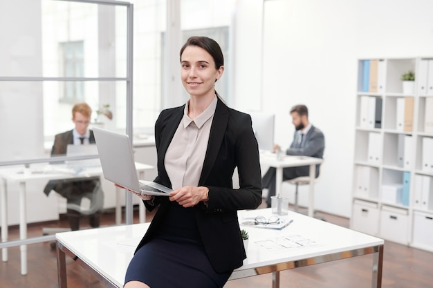 Portrait of young businesswoman holding laptop while leaning on desk in office, copy space