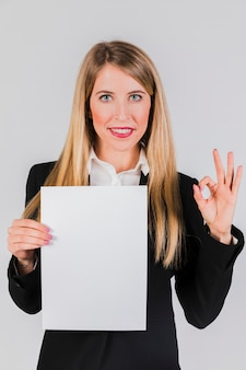 Portrait of a young businesswoman holding the white paper in hand showing ok sign