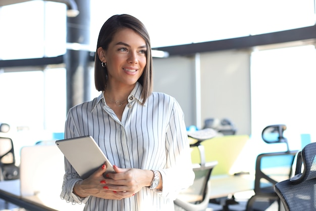 Portrait of young businesswoman looking at camera, holding touch pad while standing in modern office space interior.