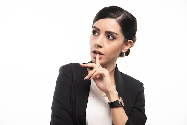 Portrait of young businesswoman posing on white wall.