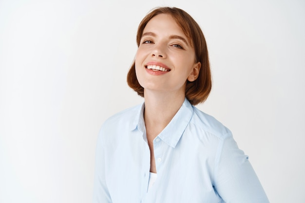 Portrait of young businesswoman smiling on white wall. female entrepreneur in office blouse, standing motivated and self-assured