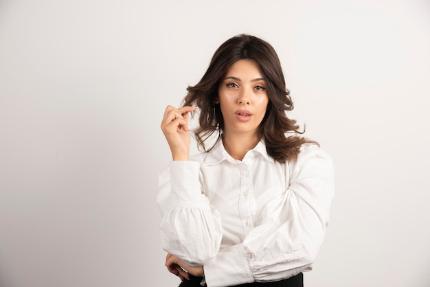Portrait of young businesswoman standing on white.
