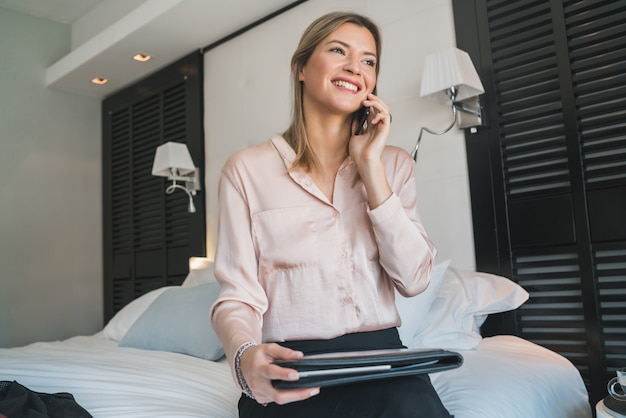 Portrait of young businesswoman talking on the phone at the hotel room. business travel concept.