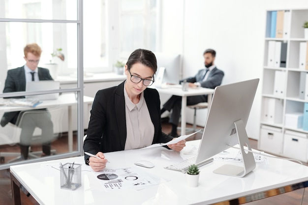 Portrait of young businesswoman wearing glasses taking notes while working at desk in office, accountant or manager concept