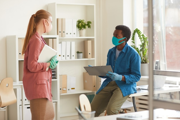 Portrait of young businesswoman wearing mask and gloves talking to african-american colleague while working in post pandemic office