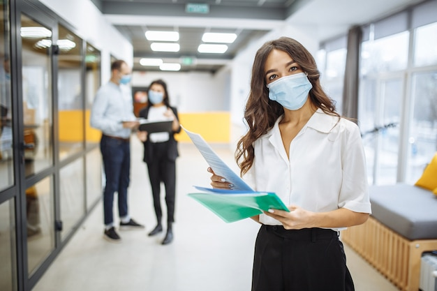 Portrait of a young businesswoman wearing a medical mask checking papers and business trends and prospects at an office corridor.